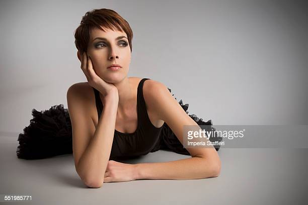 Studio portrait of woman lying on floor wearing black tutu