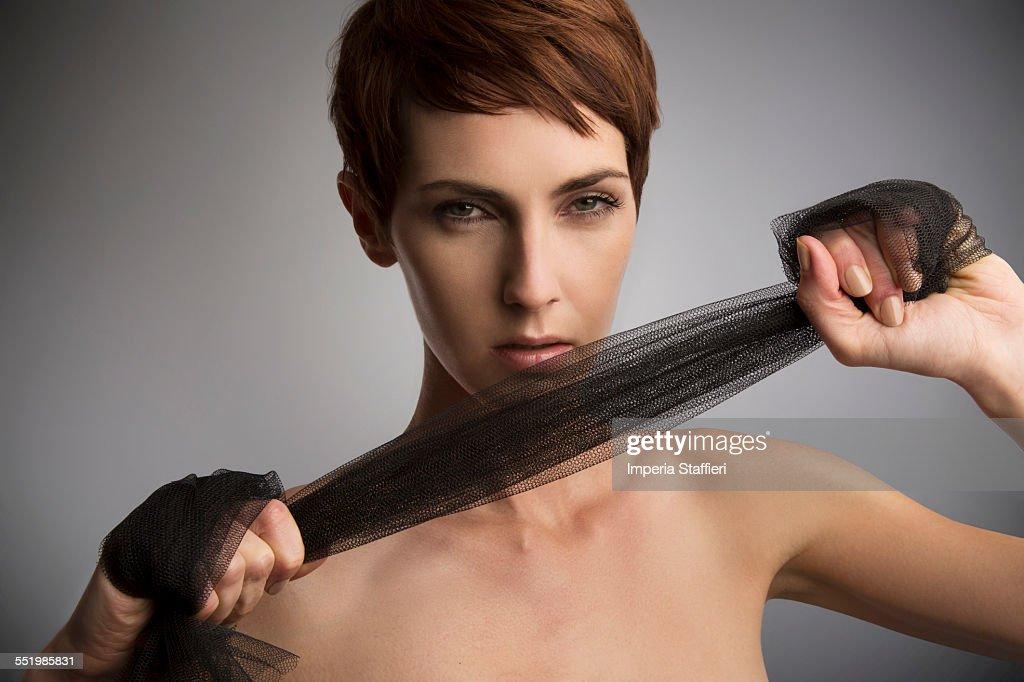 Studio portrait of woman pulling black silk scarf around hands