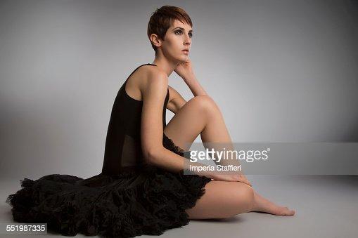 Studio portrait of woman sitting on floor wearing black tutu