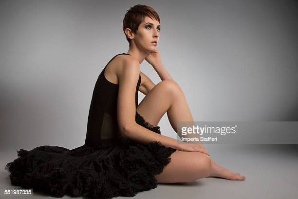 Studio portrait of woman sitting on floor wearing black tutu