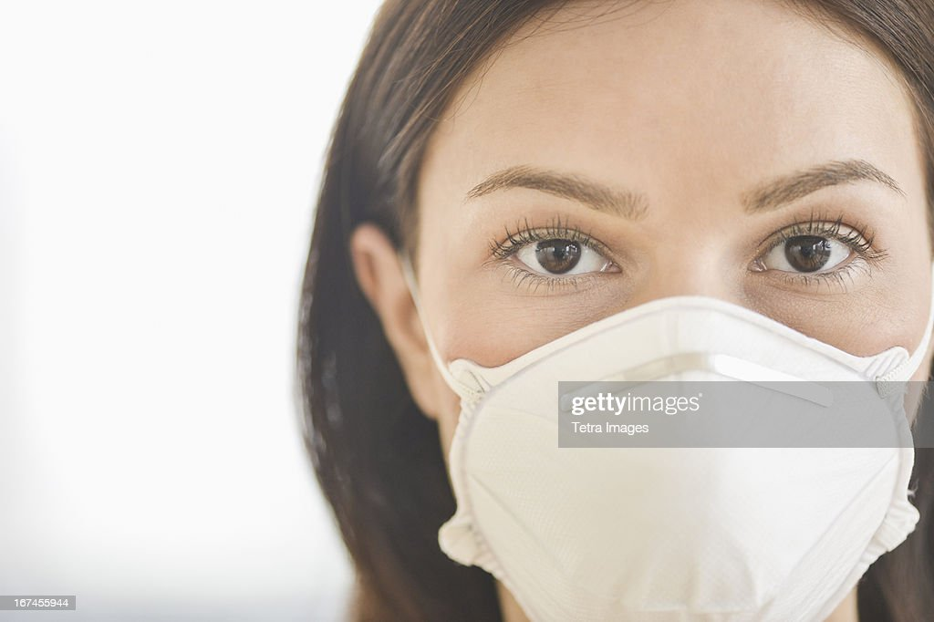 Studio portrait of woman wearing flu mask : Stock Photo