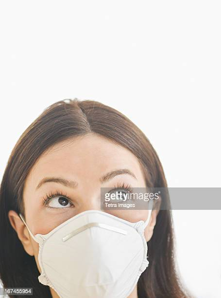 Studio portrait of woman wearing flu mask