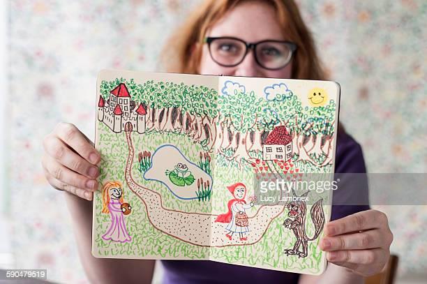 Studio portrait of young artist showing her work