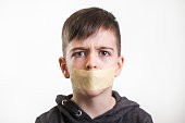 Studio portrait of young boy with adhesive tape over his mouth