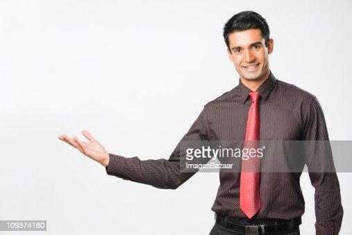 Studio portrait of young businessman extending arm : Stock Photo