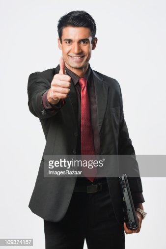 Studio portrait of young businessman gesturing : Stock Photo