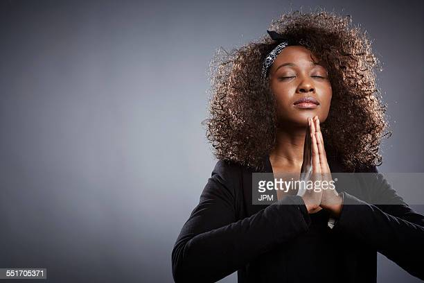 Studio portrait of young businesswoman praying