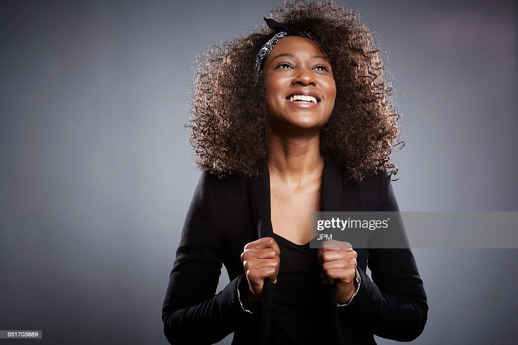 Studio portrait of young businesswoman with fists clenched