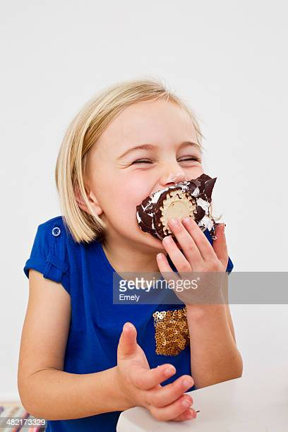 Studio portrait of young girl eating chocolate marshmallow