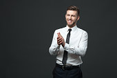 Studio portrait of young happy handsome businessman claping hands isolated on dark background.