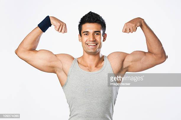 Studio portrait of young man flexing muscles