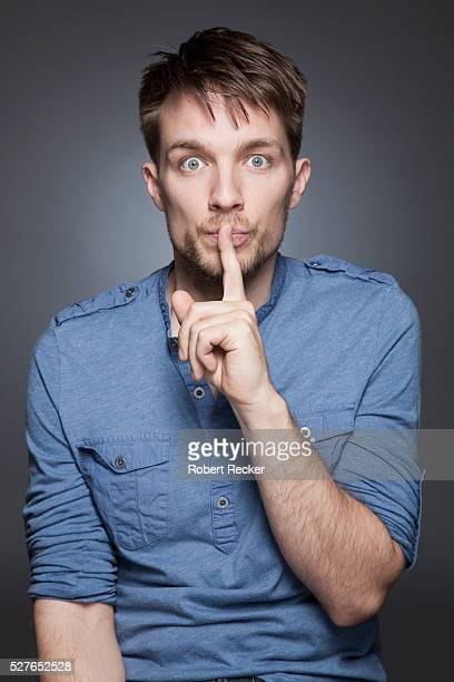 Studio portrait of young man with finger on his lips