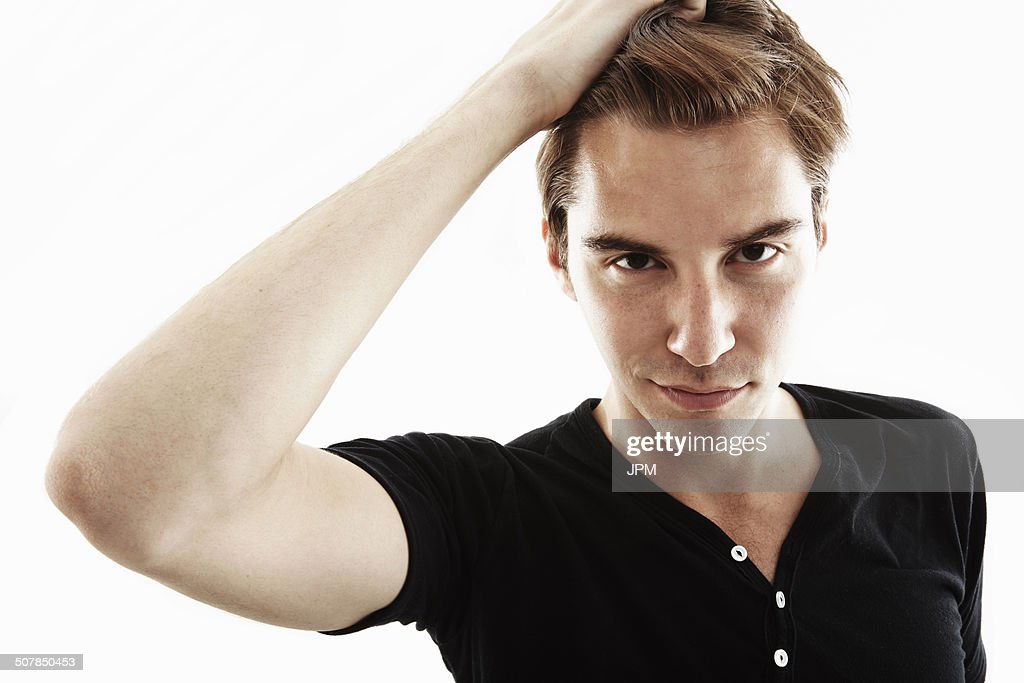 Studio portrait of young man with hand in hair