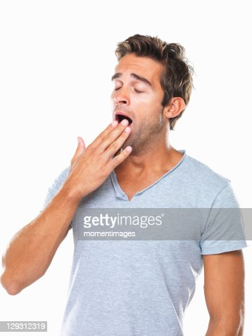 Studio portrait of young man yawning