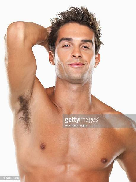 Studio portrait of young muscular man with hand in hair