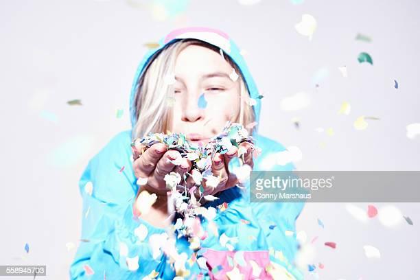Studio portrait of young woman blowing confetti