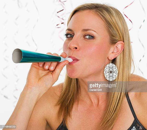 Studio portrait of young woman blowing party horn