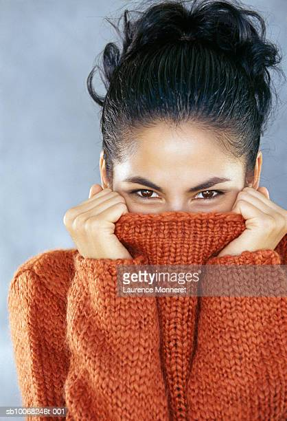 Studio portrait of young woman covering face with turtleneck collar