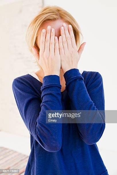 Studio portrait of young woman hiding behind hands