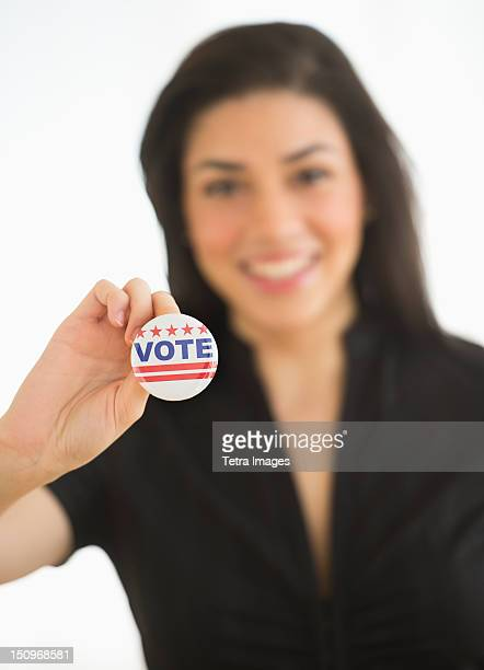 Studio portrait of young woman holding election badge