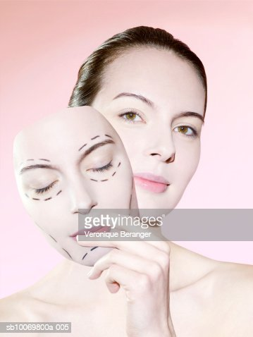 Studio portrait of young woman holding face (Digital Composite) : Stock Photo