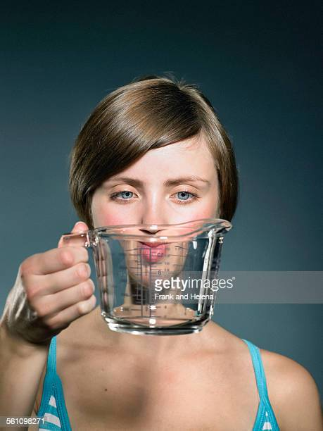 Studio portrait of young woman holding up glass measuring jug in front of face