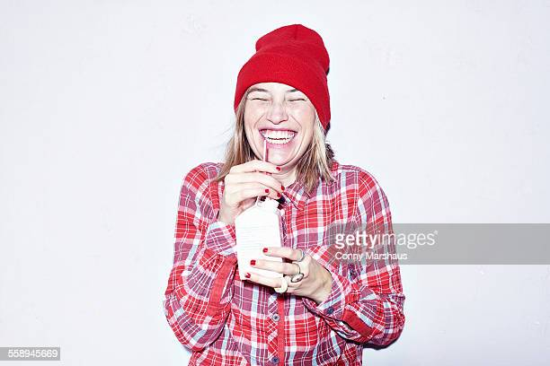 Studio portrait of young woman in red hat drinking juice