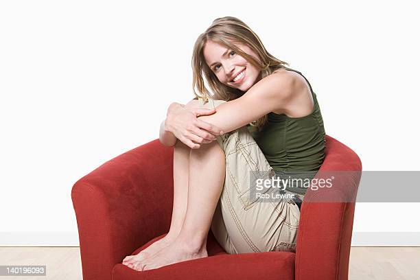 Studio portrait of young woman sitting on armchair