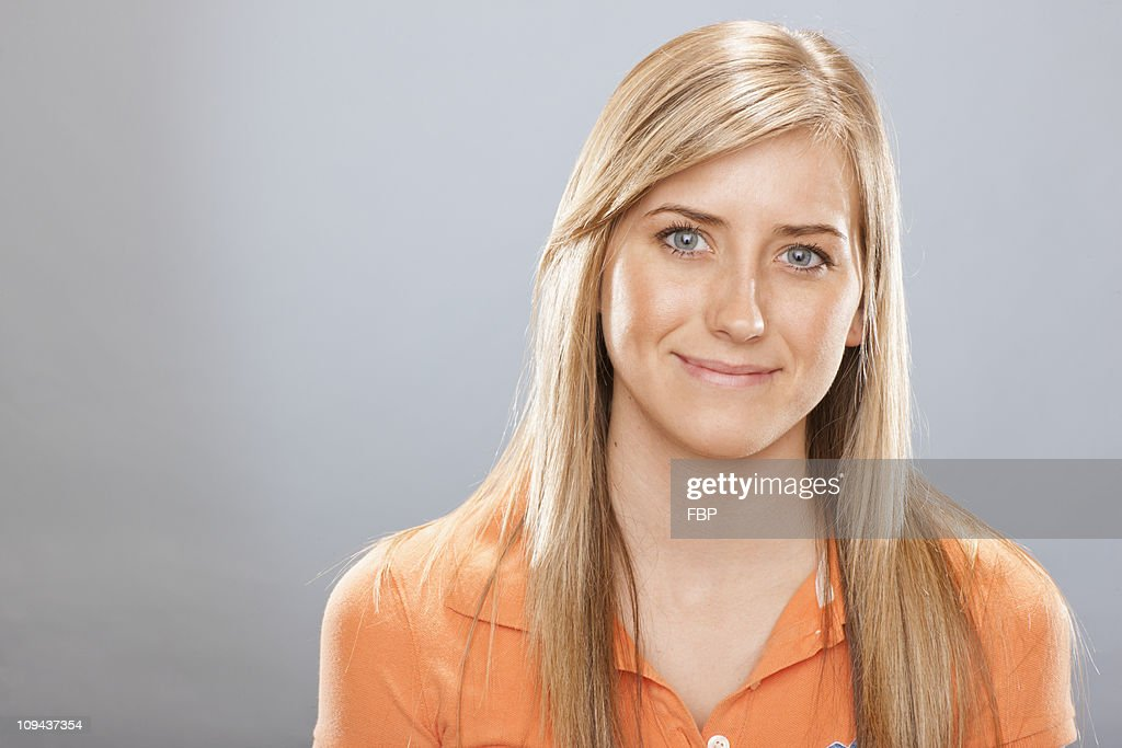 Studio portrait of young woman smiling : Stock Photo