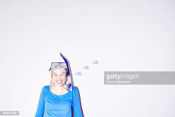 Studio portrait of young woman wearing goggles and snorkel mask
