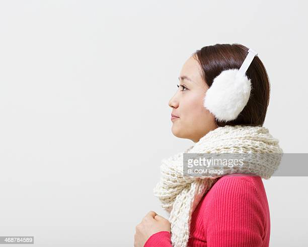 Studio portrait of young woman wearing woolen scarf and earmuffs