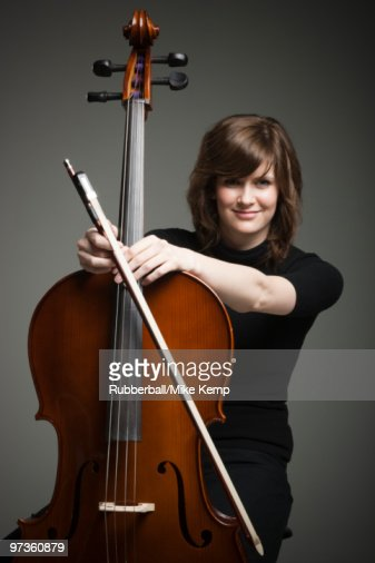 Studio portrait of young woman with cello