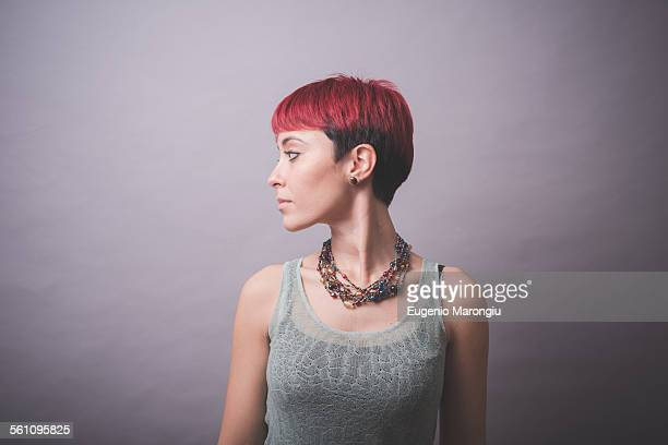 Studio portrait of young woman with short pink hair looking over her shoulder