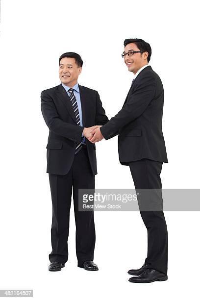 studio shot business men shaking hands