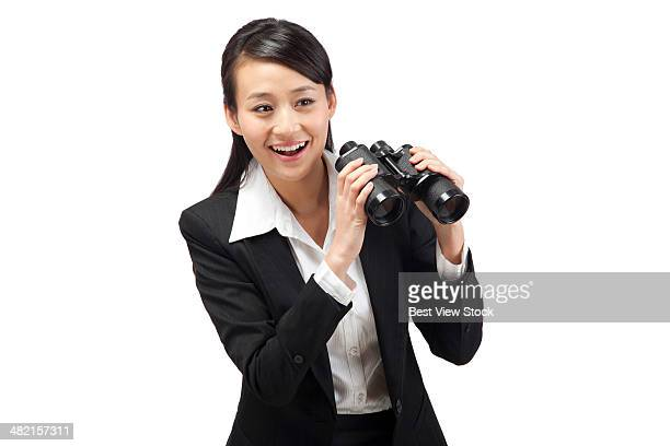 studio shot business woman looking outside using binoculars
