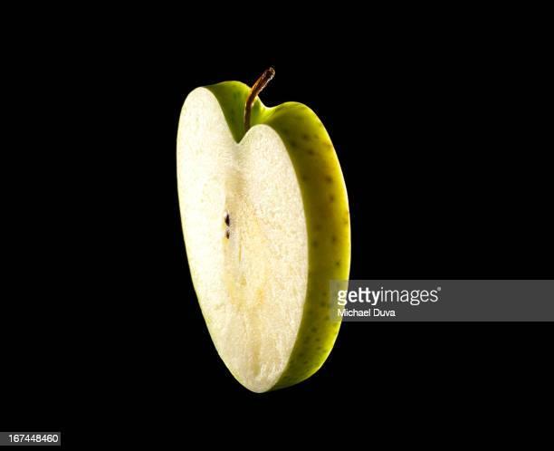 studio shot of a heart shaped  green apple