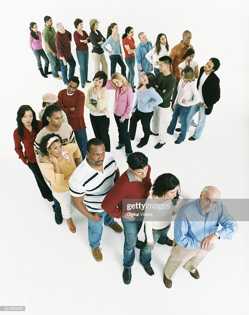Studio Shot of a Large Mixed Age, Multiethnic Group of Men and Women Waiting in Line, Senior Man at the Front of the Queue Checking the Time : Stock Photo