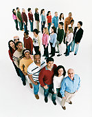 Studio Shot of a Large Mixed Age, Multiethnic Group of Men and Women Waiting in Line, Looking up at the Camera and Smiling