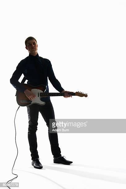 Studio shot of a man playing an electric guitar