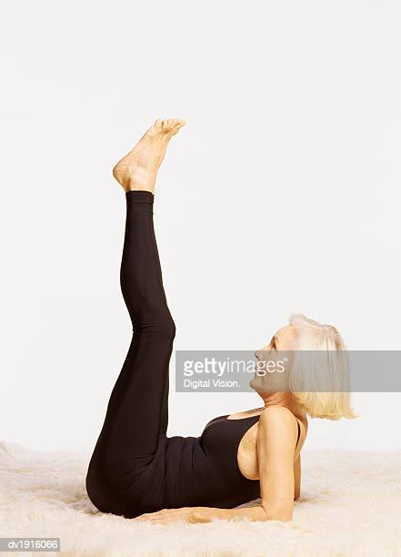 Studio Shot of a Senior Woman Exercising on a Rug, with Her Feet Raised in the Air