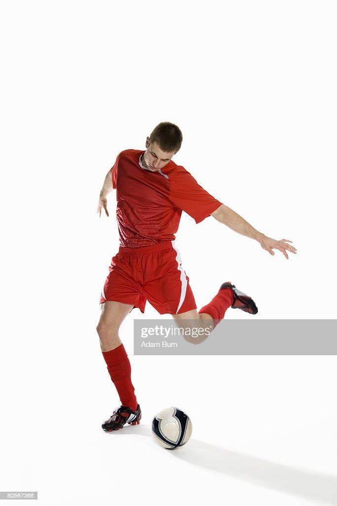 Studio shot of a soccer player kicking a soccer ball