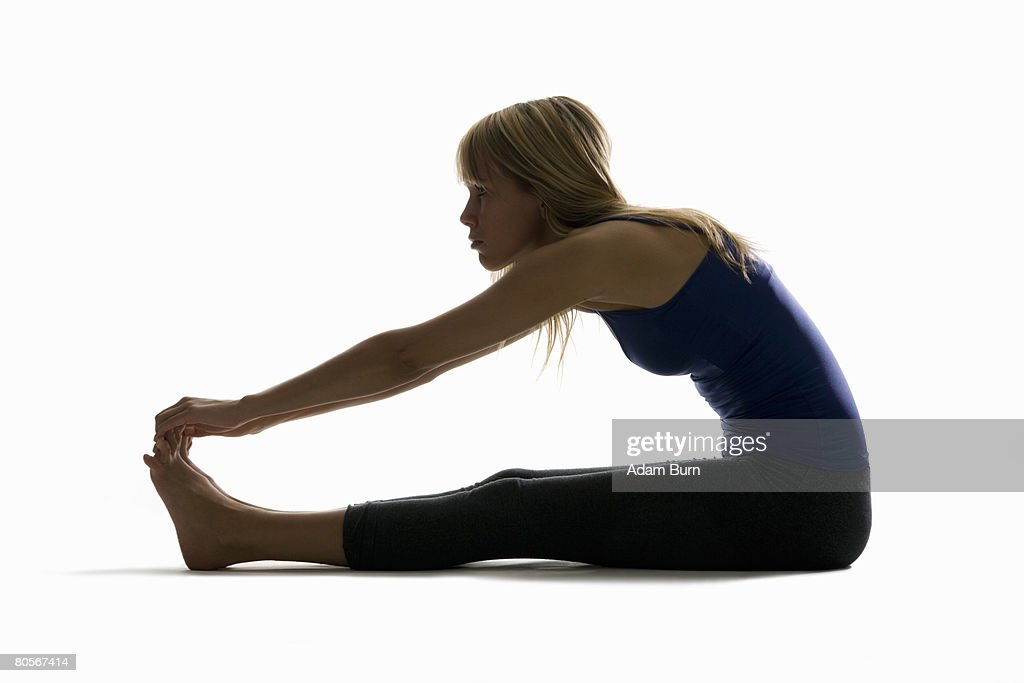 Studio shot of a woman stretching and touching her toes