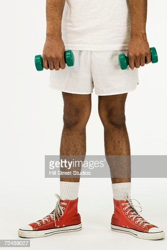 Studio shot of African man holding small dumbbells
