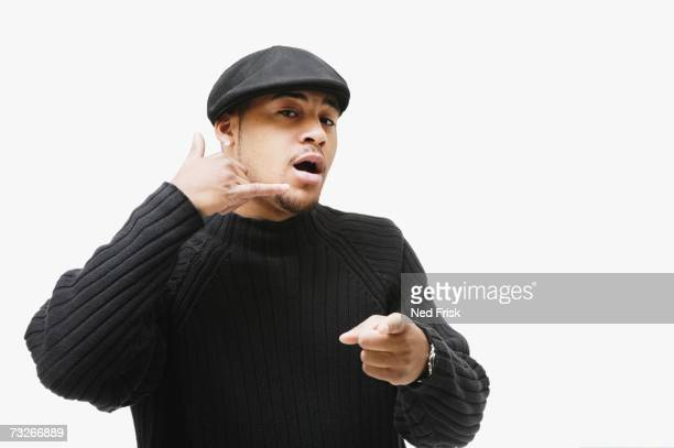 Studio shot of African man making telephone hand gesture and pointing