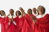 Studio shot of African men and women in choir gowns singing