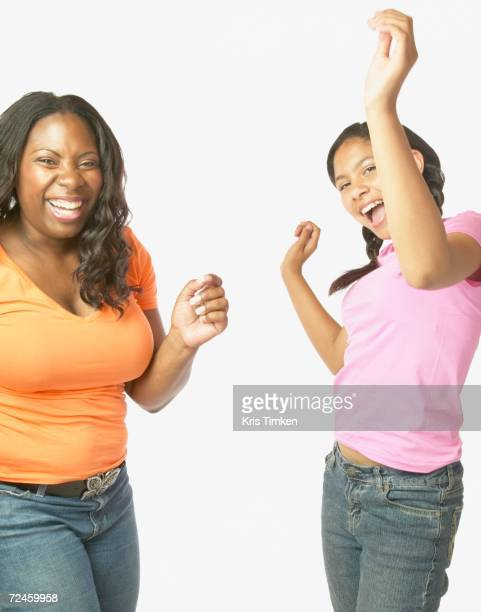 Studio shot of African mother and daughter dancing and laughing
