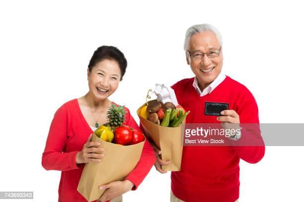 Studio shot of an elderly couple food shopping