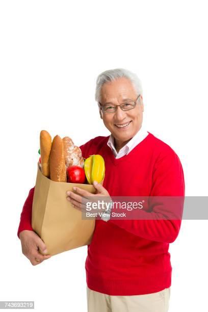 Studio shot of an old man purchasing food