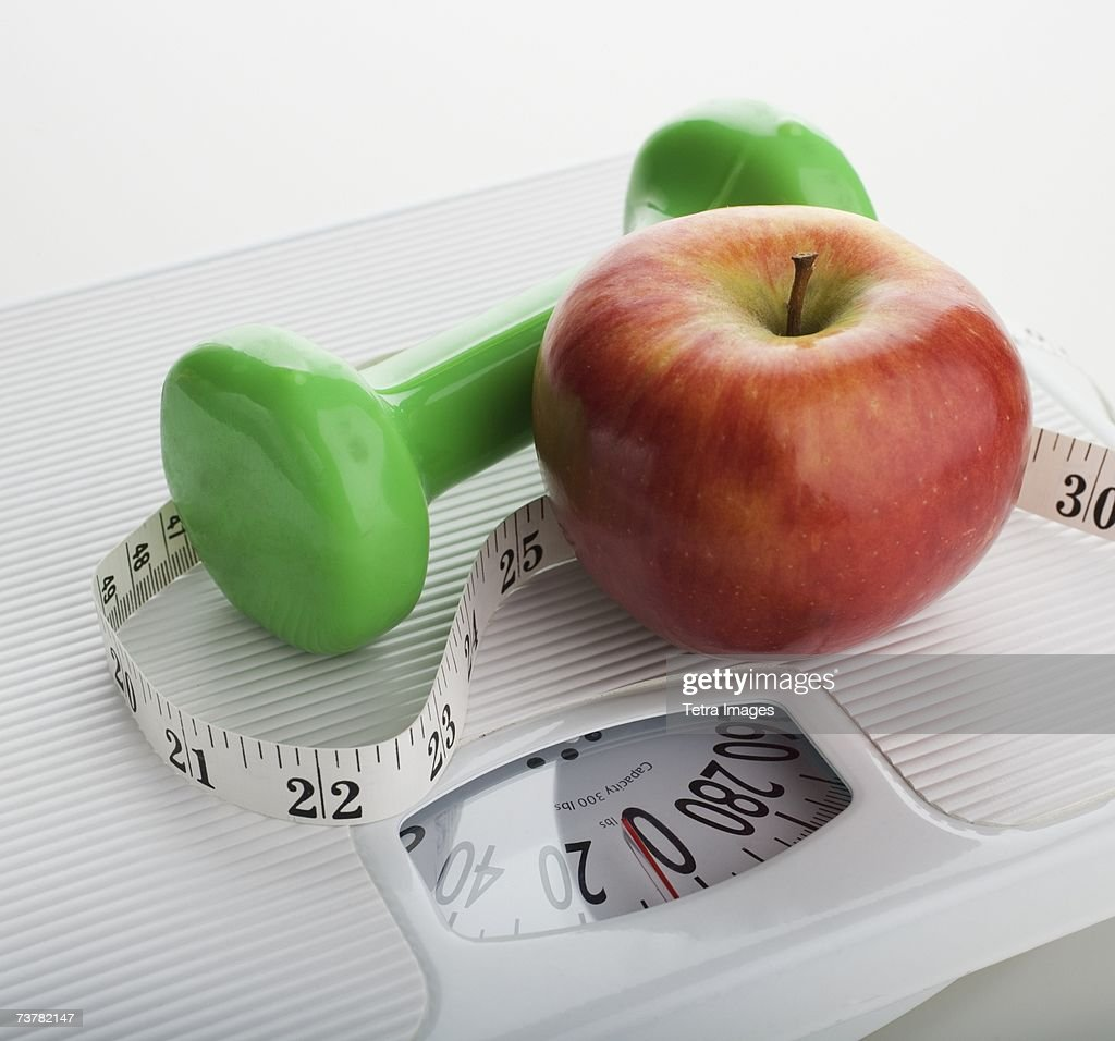 Studio shot of apple, scale, tape measure and dumbbell : Stock Photo
