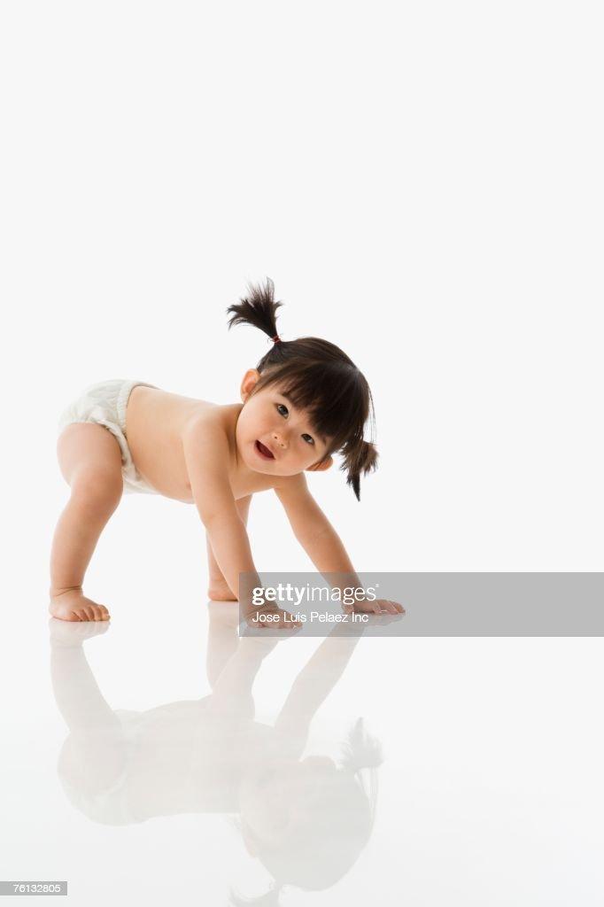 Studio shot of Asian baby crawling